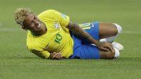 Brazilská superhvězda Neymar se svíjí v bolestech na zemi.