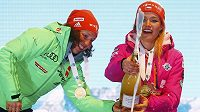 Němka Laura Dahlmeierová (vlevo) pomáhá Gabriele Koukalové při manipulaci se šampaňským na stupních vítězů po nedělní stíhačce.