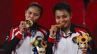 Greysia Poliiová a Apriyani Rahayuová z Indonésie pózují se zlatými medailemi.