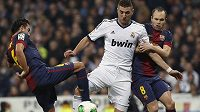 Karim Benzema z Realu Madrid bojuje s bránícími hráči Barcelony Xavim (vlevo) a Andrésem Iniestou.