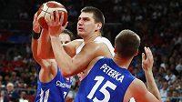 Srbský dlouhán Nikola Jokič se snaží proklouznout mezi dvojblokem Martin Peterka, Vojtěch Hruban.