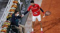 Novak Djokovič se omlouvá čárovému sudímu, kterého nechtěně trefil míčkem.