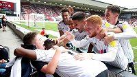 Fotbalisté Fulhamu slaví branku s mladým fanouškem na invalidmím vozíku Rhysem Porterem.