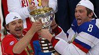 Ruský kouč Oleg Znarok (vlevoú a Alexandr Ovečkin pózují se zlatými medailemi a pohárem pro mistry světa v Minsku. Ruský trenér byl ale pro utkání distancován.
