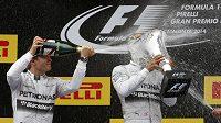 Nico Rosberg (vlevo) kropí šampaňským Lewise Hamiltona po triumfu ve Velké ceně Španělska.