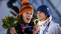 Nizozemská rychlobruslařka Ireen Wüstová se zlatou olympijskou medailí ze závodu na 3000 m. V pozadí stříbrná Martina Sáblíková.