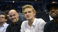 Zpěvák a plavec Cody Simpson (druhý zprava) na snímku při sledování zápasu NBA v Orlandu.