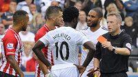 Útočník Swansea Bony Wilfried přihlíží, jak sudí Jonathan Moss vytahuje červenou kartu.
