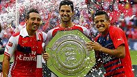 Fotbalisté Arsenalu zleva Santi Cazorla, Mikel Arteta a Alexis Sánchez s trofejí pro vítěze anglického Superpoháru Community Shield.