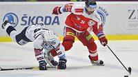 Plzeňský hokejista Vojtěch Němec padá na ledovou plochu, Zbyněk Irgl z Olomouce míří za pukem během čtvrtfinále play off hokejové extraligy.