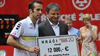 Radek Štěpánek (vlevo) předává šek šéftrenérovi Tenisového klubu Sparta Praha Davidu Kunstovi. Peníze jsou určené na pomoc při obnově povodní zničeného pražského areálu.
