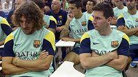 Fotbalisté Barcelony Lionel Messi a Carles Puyol (vlevo) na tiskové konferenci, kde prezident Sandro Rossel oznámil konec trenéra Vilanovy kvůli rakovině.
