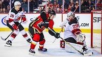 Gólman New Jersey Devils zasahuje proti útočícímu hráči Flames Johnnymu Gaudreauovi. Utkání vyhráli Flames poměrem 9:4.