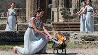 Herečka Xanthi Georgiuová představující vrchní kněžku tradičně zapálila olympijský oheň pomocí zrcadla a slunečních paprsků.