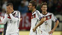 Zklamaní němečtí fotbalisté zleva Lukas Podolski, Thomas Müller a Eric Durm po úterní remíze 1:1 s Irskem.