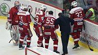 Slávističtí hokejisté odvádějí z ledu zraněného spoluhráče Antonína Růžičku.