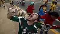 Fanoušek Mexika slaví úspěch svého týmu v duelu proti Brazílii lahví tequily.