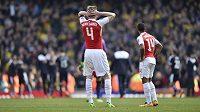 Obránce Arsenalu Per Mertesacker a jeho spoluhráč Theo Walcott sledují radost hráčů Watfordu.