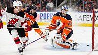 Blake Coleman (vlevo) z New Jersey Devils překonává brankáře Edmontonu Oilers Anthonyho Stolarze v utkání NHL.