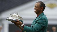 Tiger Woods s tradičním zeleným sakem pro vítěze a trofejí.