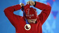 Švýcarský běžec na lyžích Dario Cologna pózuje se zlatou medailí ze závodu na 15 km klasicky.