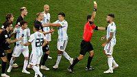 Argentinec Nicolas Otamendi dostává žlutou kartu za nakopnutí míče do Ivana Rakitiče.