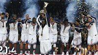 James Harden zvedá trofej pro mistry světa před zbytkem týmu USA.