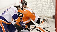 Ilja Bryzgalov se v brance Philadelphie snaží zlikvidovat v utkání NHL šanci Matta Moulsona z New York Islanders.