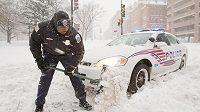 Washingtonský policista doluje ze závěje svůj vůz. Hlavní město USA ochromila mohutná sněhová bouře.