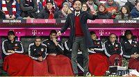 Trenér Bayernu Pep Guardiola v červeném puloveru při zápase se Schalke.