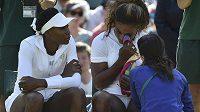 Serena Williamsová (vpravo) v péči lékařky při utkání wimbledonské čtyřhry. Vlevo sestra americké hráčky Venus.
