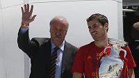 Trenér španělských fotbalistů Vicente del Bosque (vlevo) zdraví společně s kapitánem Ikerem Casillasem fanoušky na letišti v Madridu.