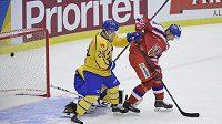 Český hokejista Lukáš Radil (vpravo) cloní před bránou, zatímco puk po střele Jakuba Nakládala končí v síti švédské branky.