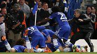 Útočník Chelsea Demba Ba v objetí spoluhráčů a kouče Joseho Mourinha poté, co vstřelil postupový gól Chelsea do semifinále Ligy mistrů.