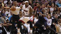 Lebron James (vlevo) z Miami Heat si kryje míč před Michaelem Kiddem-Gilchristem z týmu Charlotte Bobcats.