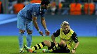 Zraněný obránce Dortmundu Marcel Schmelzer a útočník Petrohradu Hulk (vlevo).