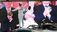 Pilot Lewis Hamilton ze stáje Mercedes oslavuje na svém voze triumf ve Velké ceně Abú Zabí F1.