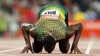 Usain Bolt líbá dráhu stadiónu v Londýně po vítězství v běhu na 100 metrů.