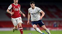 Ruben Dias z Manchesteru City v zápase Premier League s Arsenalem, vzadu jeho počínání sleduje Granit Xhaka.