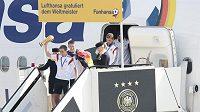 Kapitán Philipp Lahm s trofejí jako první opustil letadlo. Za ním Bastian Schweinsteiger.