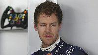 Zamyšlený Sebastian Vettel v garáži Red Bullu v Sepangu.