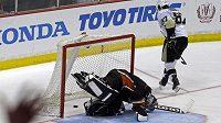 Gólman Anaheimu Jonas Hiller marně hledá puk ve výstroji po nájezdu kapitána Pittsburghu Sidneyho Crosbyho.