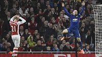 Útočník Manchesteru United Wayne Rooney (vpravo) se raduje z branky, kterou do vlastní sítě Arsenalu vstřelil Kieran Gibbs. Vlevo smutný Calum Chambers.