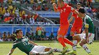 Nešťastný střet Héctora Morana s Arjenem Robbenem v závěru první půle osmifinálového duelu na MS. Vpravo je mexický kapitán Rafael Márquez.