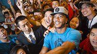 Hvězda Chicago Bulls Derrick Rose (v modrém tričku) při nedávné návštěvě Číny.