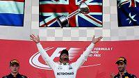Lewis Hamilton slaví s trofejí pro vítěze japonské velké ceny.