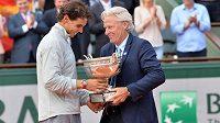 Giganti z Roland Garros. Někdejší tenisový šampión Björn Borg (vpravo) předává vítěznou trofej současnému antukovému králi Španělu Rafaelu Nadalovi.