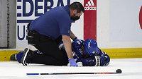 Zraněný český hokejista Jan Rutta leží na ledě během pátého semifinále play off NHL. Pomoci se mu snaží Tom Mulligan.