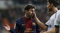 Zklamaného Lionela Messiho (vlevo) uklidňuje Xabi Alonso z Realu.