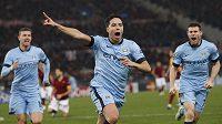 Fotbalisté Manchesteru City slaví gól na hřišti AS Řím. Uprostřed se raduje střelec branky Samir Nasri. Vlevo je útočník Edin Džeko, vpravo pak James Milner.